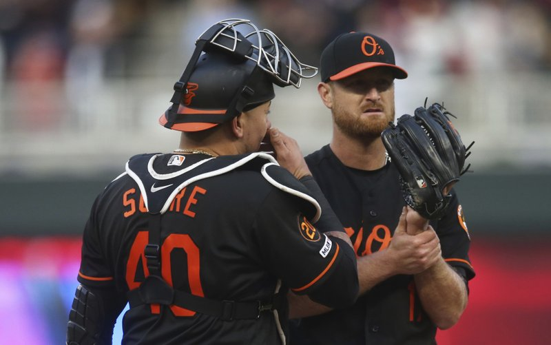 Baltimore Orioles catcher Jesus Sucre, left, visits at the mound with pitcher Alex Cobb after Cobb gave up three solo home runs in a row by the Minnesota Twins in the first inning of a baseball game Friday, April 26, 2019, in Minneapolis. (AP Photo/Jim Mone)
