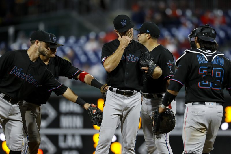 Miami Marlins relief pitcher Tyler Kinley, center, wipes his face as he is pulled during the eighth inning of a baseball game against the Philadelphia Phillies, Friday, April 26, 2019, in Philadelphia. (AP Photo/Matt Slocum)
