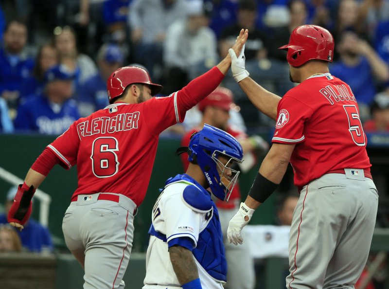 Los Angeles Angels' David Fletcher (6) high-fives teammate Albert Pujols (5) after Pujols' two-run home run during the first inning of a baseball game against the Kansas City Royals at Kauffman Stadium in Kansas City, Mo. (AP Photo/Orlin Wagner)