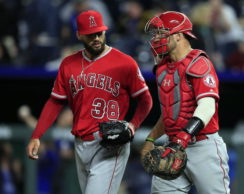 Los Angeles Angels relief pitcher Justin Anderson (38) walks off the field with catcher Kevan Smith (44) following a baseball game against the Kansas City Royals at Kauffman Stadium in Kansas City, Mo. (AP Photo/Orlin Wagner)