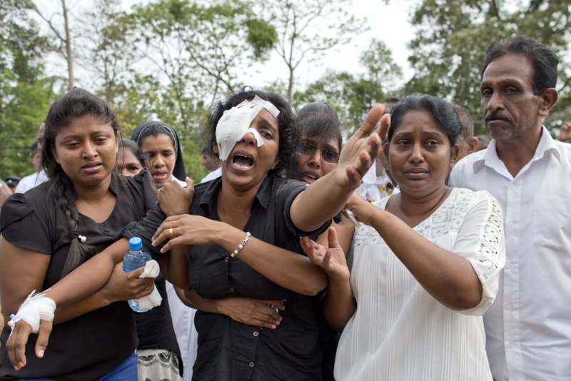FILE- In this Wednesday, April 24, 2019 file photo, Anusha Kumari, center, weeps during a mass burial for her husband, two children and three siblings, all victims of Easter Sunday's bomb attacks, in Negombo, Sri Lanka. (AP Photo/Gemunu Amarasinghe, File)