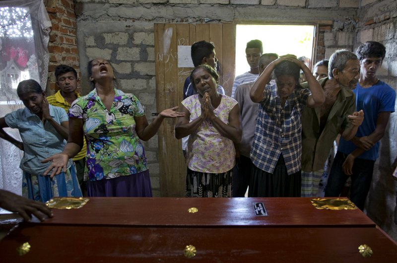FILE - In this Monday, April 22, 2019 file photo, relatives weep by the coffin of 12-year Sneha Savindi, a victim of Easter Sunday's bombing at St. (AP Photo/Gemunu Amarasinghe, File)