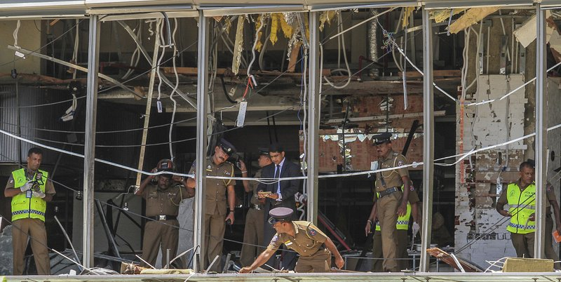 FILE - In this Sunday April 21, 2019, file photo, a Sri Lankan Police officer inspects a blast spot at the Shangri-la hotel in Colombo, Sri Lanka. (AP Photo/Chamila Karunarathne, file)