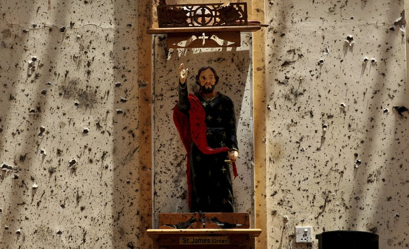 FILE- In this Thursday, April 25, 2019 file photo, a statue of St. James stands on a wall speckled with fragments of shrapnel at St. (AP Photo/Manish Swarup, File)
