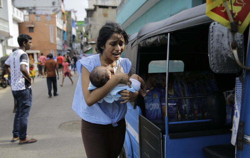 FILE - In this Monday, April 22, 2019 file photo, a Sri Lankan woman, who lives near St. Anthony's shrine, runs for safety with her infant after police found explosive devices in a parked vehicle in Colombo, Sri Lanka. (AP Photo/Eranga Jayawardena)