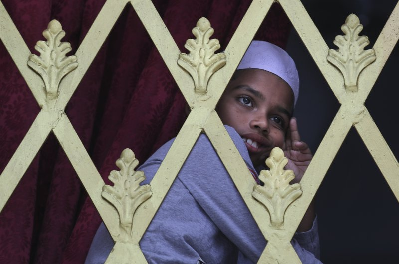 FILE - In this Friday, April 26, 2019 file photo, a Sri Lankan Muslim boy looks out from the window of a Mosque before Friday prayers in Colombo, Sri Lanka. (AP Photo/Manish Swarup, File)