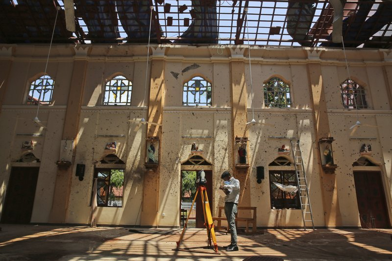 FILE - In this Thursday, April 25, 2019 file photo, sunlight steams in from gaping holes, as a surveyor works at St. (AP Photo/Manish Swarup, File)