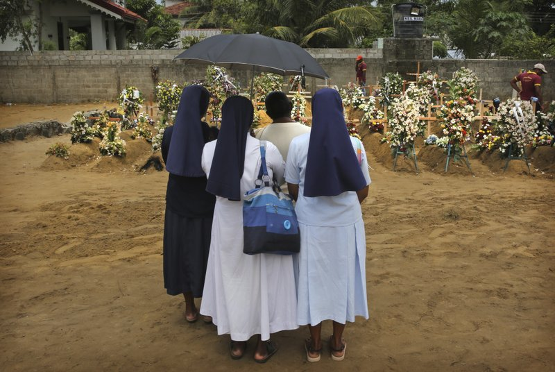 FILE - In this Thursday, April 25, 2019 file photo, Catholic nuns stand with a relative of a victim of Easter Sunday's bomb blast at St. (AP Photo/Manish Swarup, File)