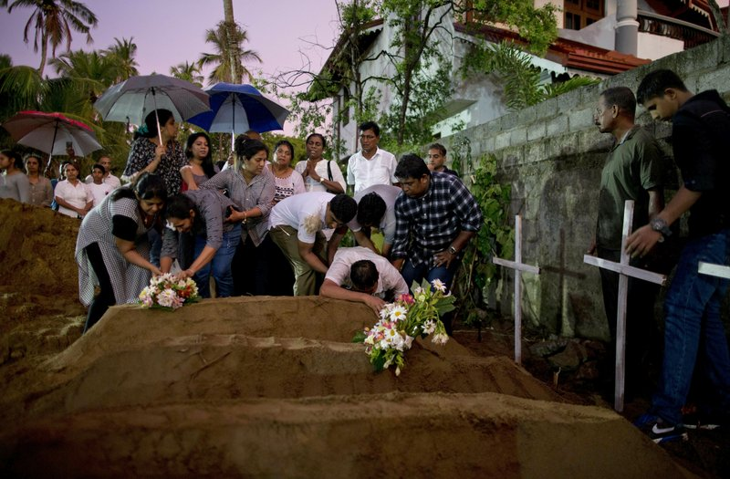 FILE - In this Monday, April 22, 2019 file photo, relatives place flowers after the burial of three from the same family, all victims of Easter Sunday's bomb blast at St. (AP Photo/Gemunu Amarasinghe, File)