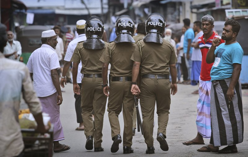 FILE- In this Friday, April 26, 2019 file photo, Sri Lankan policemen patrol a Muslim neighborhood before Friday prayers in Colombo, Sri Lanka. (AP Photo/Manish Swarup)