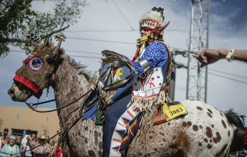 0hane Redhawk of the Lakota Nation in South Dakota rides down main street during the judging portion of the Horse and Rider Parade at the Gathering Of Nations in Albuquerque, N. (Roberto E. Rosales/The Albuquerque Journal via AP)