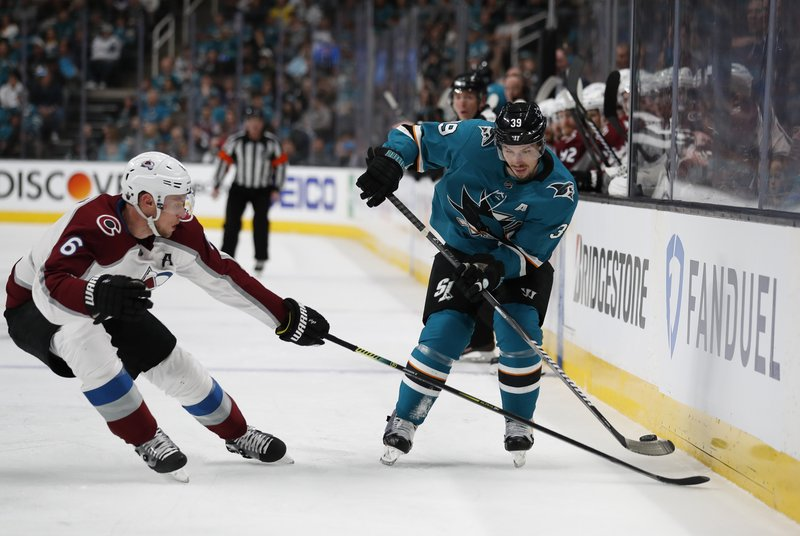 Colorado Avalanche's Erik Johnson (6) battles for the puck against San Jose Sharks' Logan Couture (39) in the first period of Game 1 of an NHL hockey second-round playoff series at the SAP Center in San Jose, Calif. (AP Photo/Josie Lepe)