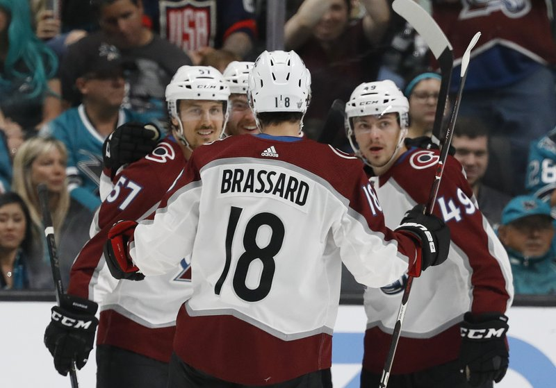 Colorado Avalanche's Gabriel Bourque (57) celebrates his goal against the San Jose Sharks with Derick Brassard (18) and Samuel Girard (49) in the first period of Game 1 of an NHL hockey second-round playoff series at the SAP Center in San Jose, Calif. (AP Photo/Josie Lepe)