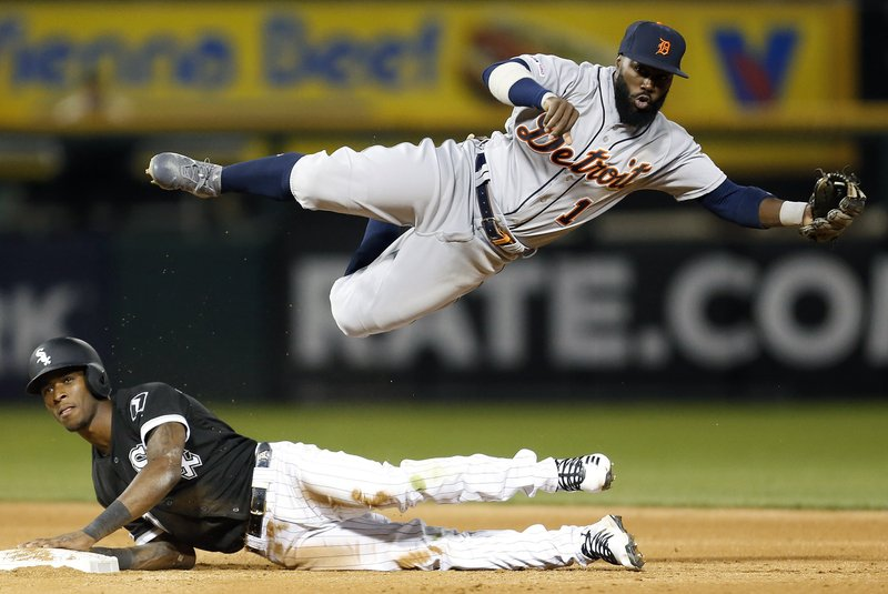 Detroit Tigers second baseman Josh Harrison (1) falls after throwing to first base while Chicago White Sox's Tim Anderson, bottom, is out on a fielder's choice during the fifth inning of a baseball game Friday, April 26, 2019, in Chicago. (AP Photo/Nuccio DiNuzzo)