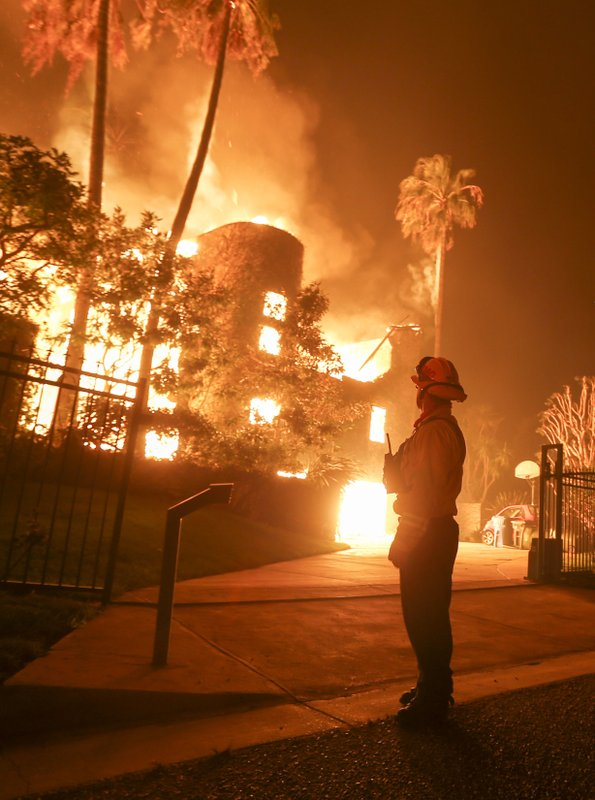 FILE - In this Nov. 9, 2018 file photo, a firefighter keeps watch as the Woolsey Fire burns a home in Malibu, Calif. (AP Photo/Ringo H.W. Chiu, File)