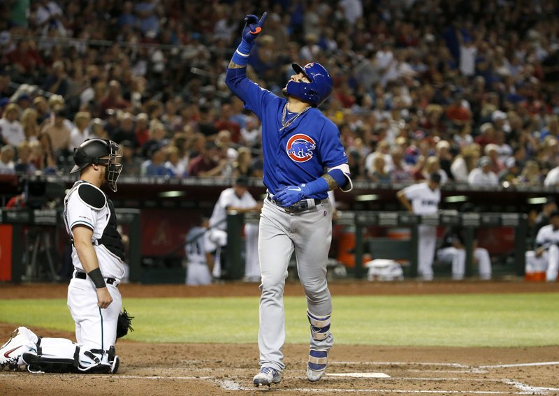 Chicago Cubs' Javier Baez, right, gestures skyward as he crosses the plate after hitting a home run against the Arizona Diamondbacks during the fourth inning of a baseball game, Friday, April 26, 2019, in Phoenix. (AP Photo/Ralph Freso)