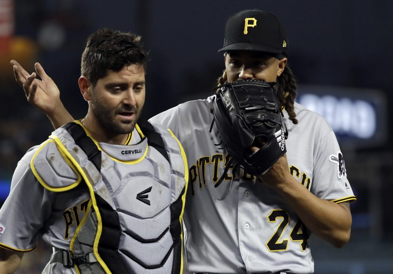 Pittsburgh Pirates starting pitcher Chris Archer, right, talks to catcher Francisco Cervelli as they walk off the field at the end of the second inning of a baseball game against the Los Angeles Dodgers Friday, April 26, 2019, in Los Angeles. (AP Photo/Marcio Jose Sanchez)