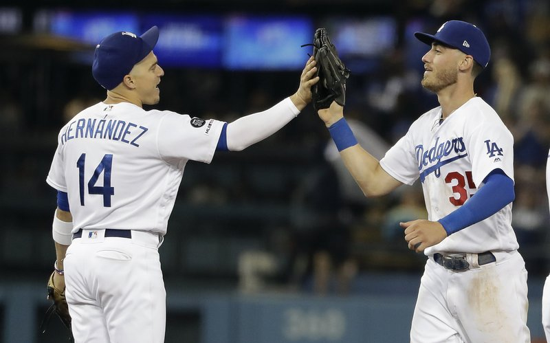 Los Angeles Dodgers' Enrique Hernandez, left, and Cody Bellinger celebrate after a win over the Pittsburgh Pirates during a baseball game Friday, April 26, 2019, in Los Angeles. (AP Photo/Marcio Jose Sanchez)