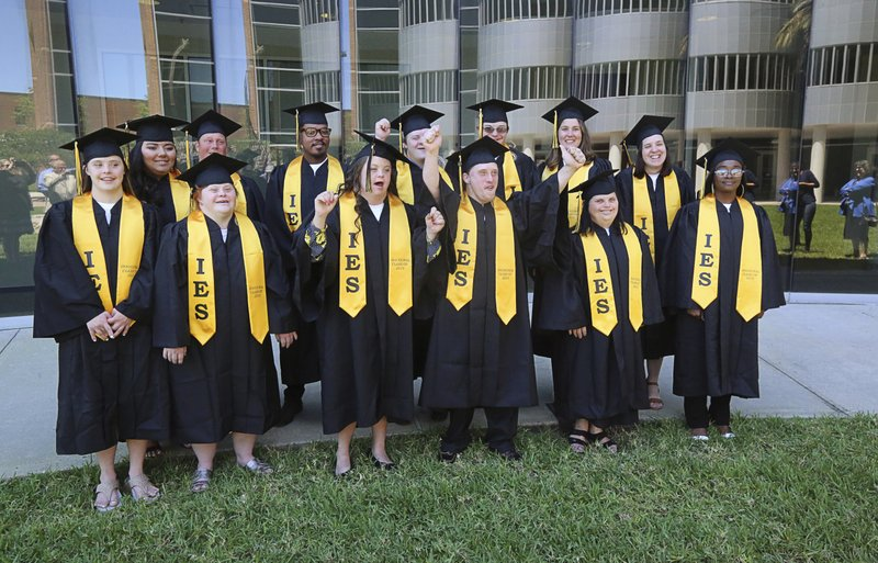 In this Monday, April 22, 2019 photo, the first graduating class from the Inclusive Education Services (IES) program at the University of Central Florida pose for a photo with their cap and gowns in Orlando, Fla. (Ricardo Ramirez Buxeda/Orlando Sentinel via AP)