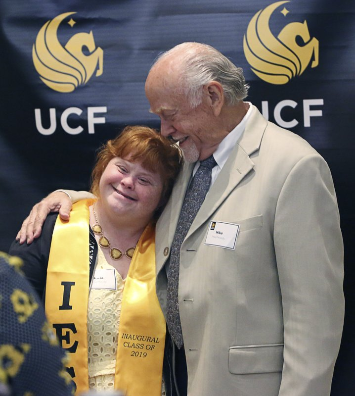 In this Monday, April 22, 2019 photo, Patricia Moody, left, gets a hug from her father Mike Moody at the University of Central Florida in Orlando, Fla. (IES) program at the University of Central Florida, (Ricardo Ramirez Buxeda/Orlando Sentinel via AP)