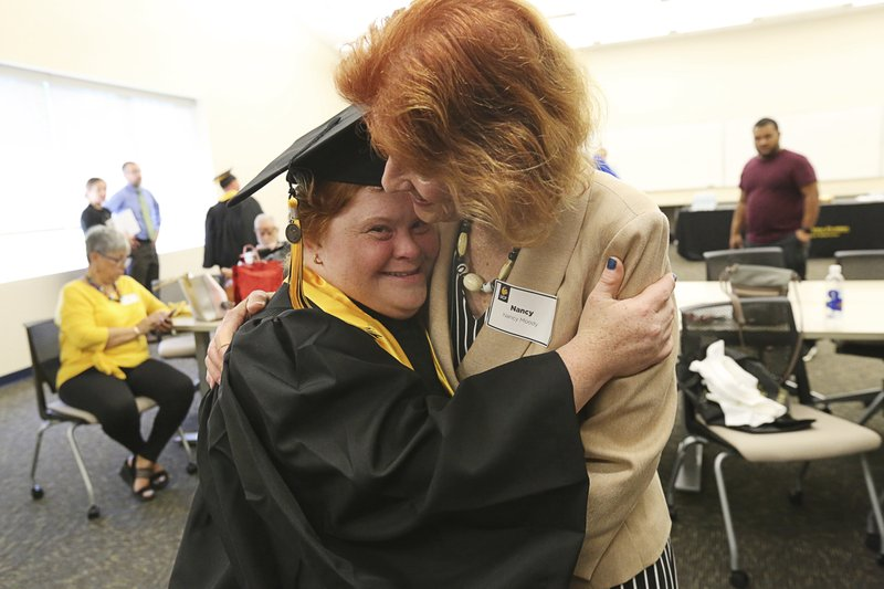 In this Monday, April 22, 2019 photo, Patricia Moody, left, gets a hug and a kiss from mom Nancy Moody at the University of Central Florida in Orlando, Fla. (IES) program at the University of Central Florida, (Ricardo Ramirez Buxeda/Orlando Sentinel via AP)