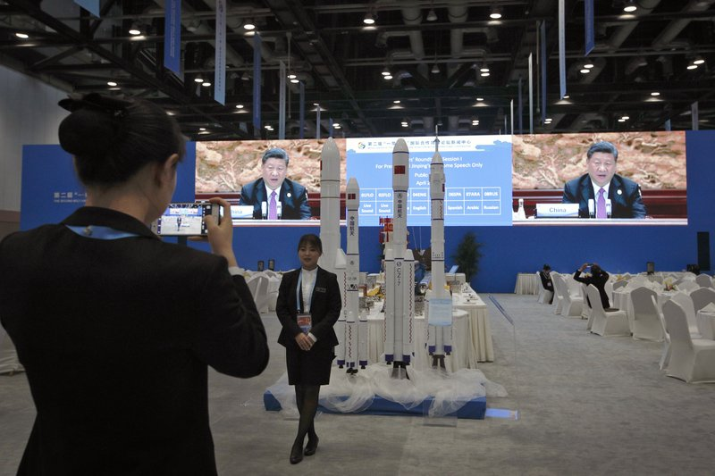 A waitress poses for a photo as Chinese President Xi Jinping is live broadcasted at the leaders summit of the Belt and Road Forum, at the media center in Beijing, Saturday, April 27, 2019. (AP Photo/Andy Wong)