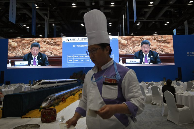 A chef prepares lunch next to the high speed train models as Chinese President Xi Jinping is live broadcasted at the leaders summit of the Belt and Road Forum, at the media center in Beijing, Saturday, April 27, 2019. (AP Photo/Andy Wong)