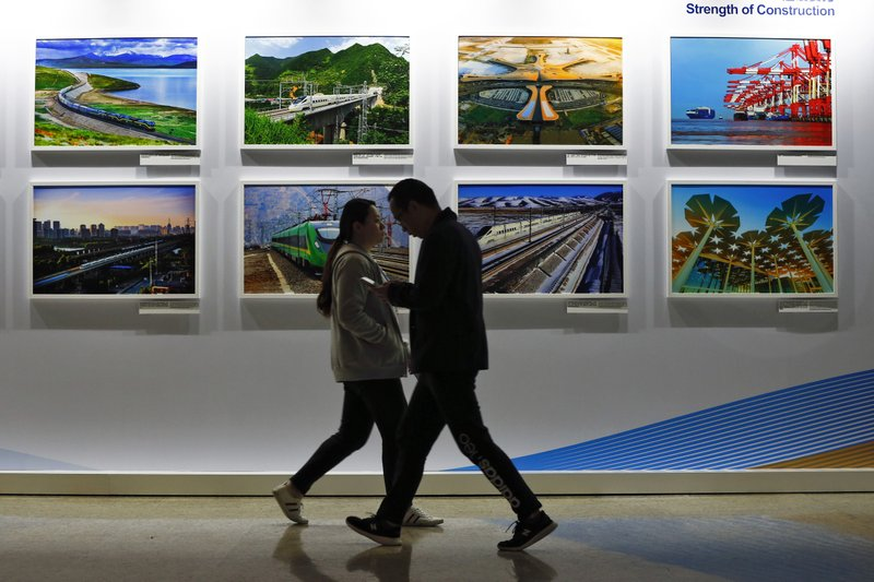 People walk by a display board showcasing China's construction projects at the media center of the Belt and Road Forum in Beijing, Saturday, April 27, 2019. (AP Photo/Andy Wong)