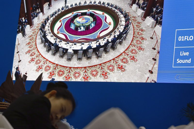 A waitress rests near a live image of leaders attending the round table summit of the Belt and Road Forum chaired by Chinese President Xi Jinping, at the media center in Beijing, Saturday, April 27, 2019. (AP Photo/Andy Wong)