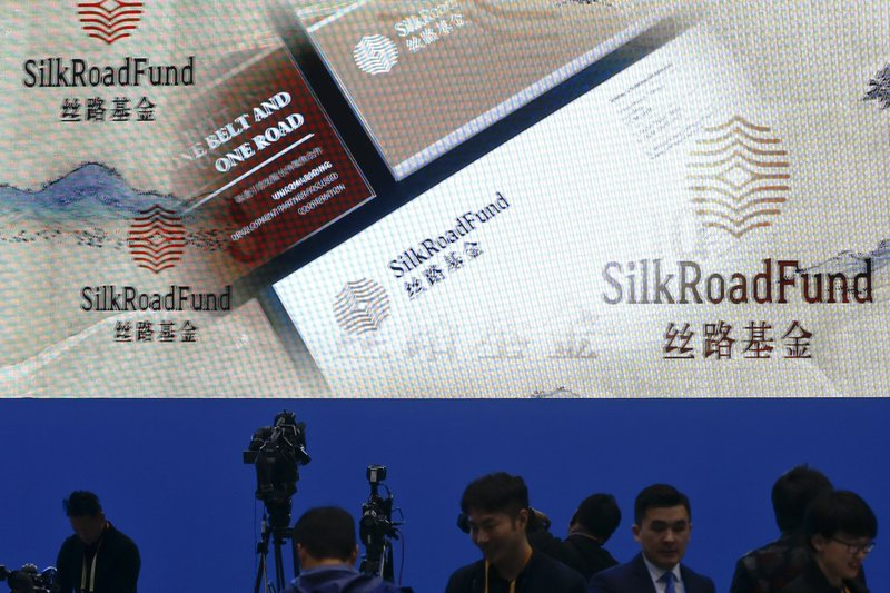 Journalists work near a screen promoting the Belt and Road Forum at the media center in Beijing, Saturday, April 27, 2019. (AP Photo/Andy Wong)