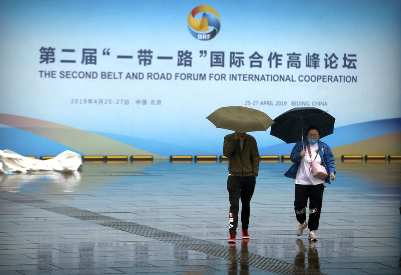 People carry umbrellas as they walk past a banner for the Belt and Road Forum at the China National Convention Center in Beijing, Saturday, April 27, 2019. (AP Photo/Mark Schiefelbein)