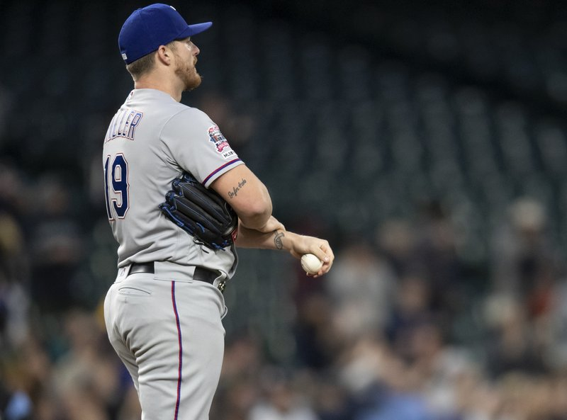 Texas Rangers starting pitcher Shelby Miller reacts after giving up a three-run home run to Seattle Mariners' Edwin Encarnacion that also scored Domingo Santana and Daniel Vogelbach during the third inning of a baseball game, Friday, April 26, 2019, in Seattle. (AP Photo/Stephen Brashear)