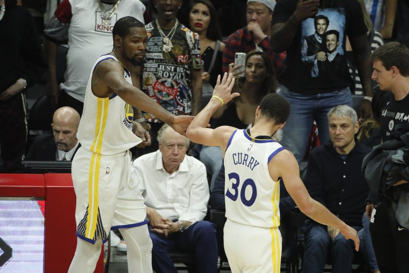 Golden State Warriors' Kevin Durant, left, and Stephen Curry high-five as they walks off the court during the second half in Game 6 of a first-round NBA basketball playoff series against the Los Angeles Clippers Friday, April 26, 2019, in Los Angeles. (AP Photo/Jae C. Hong)