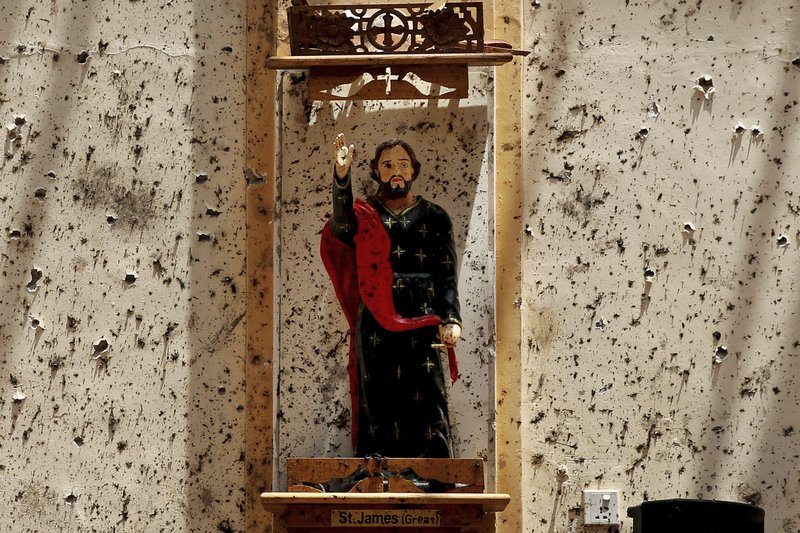 A statue of St. James stands on a wall speckled with fragments of shrapnel at St. Sebastian's Church on Thursday, April 25, 2019, where a suicide bomber blew himself up in Negombo, north of Colombo, Sri Lanka. (AP Photo/Manish Swarup)