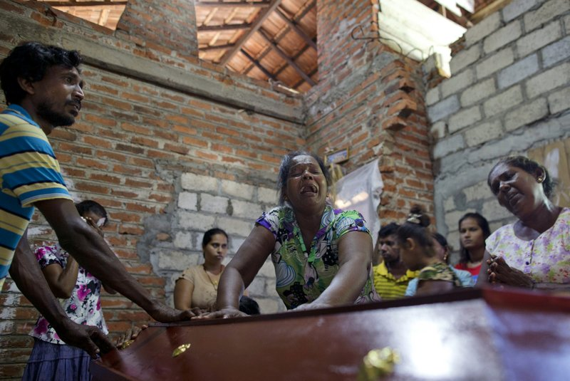 Lalitha, center, weeps over the coffin of her 12-year old niece, Sneha Savindi, who was a victim of the Easter Sunday bombing at St. (AP Photo/Gemunu Amarasinghe)