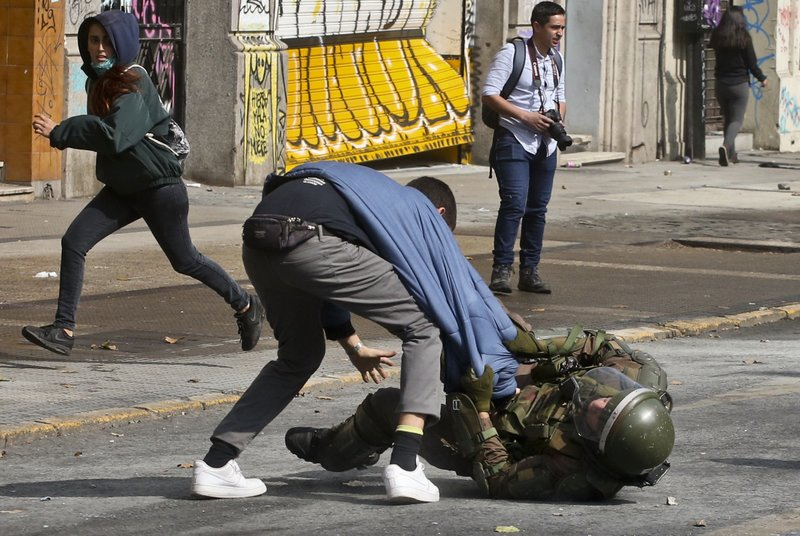 A student tries to free himself from a police officer during a protest demanding free, non-sexist education, in Santiago, Chile, Thursday, April 25, 2019. (AP Photo/Esteban Felix)