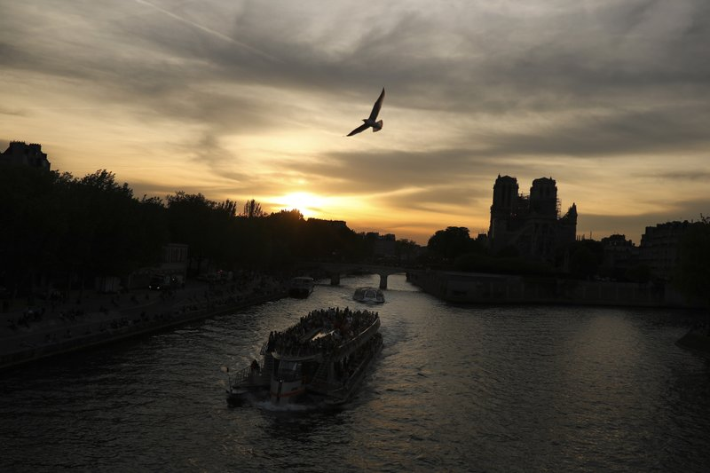 Boats with tourists aboard sail along the Seine river next to the Notre Dame Cathedral as the sun sets in Paris, Sunday, April 21, 2019. (AP Photo/Francisco Seco)