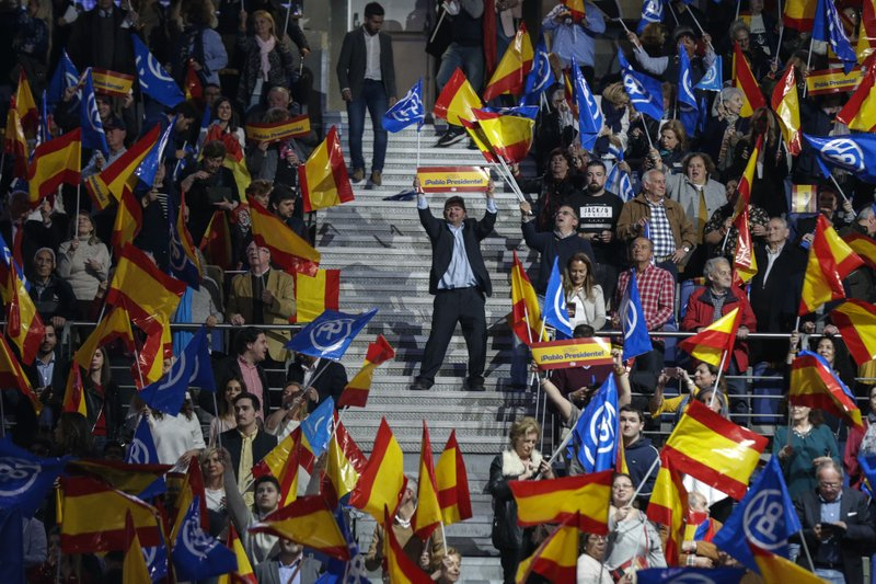 Popular Party supporters wave Spanish flags during the closing election campaign event in Madrid, Spain, Friday, April 26, 2019. (AP Photo/Andrea Comas)