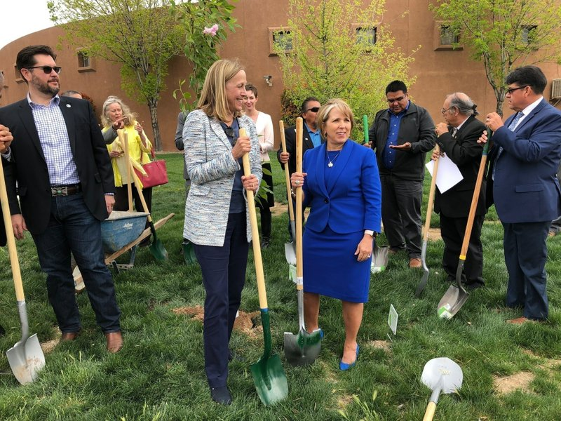 FILE - In this Monday, April 22, 2019 file photo, Gov. Michelle Lujan Grisham, center right, and PNM Resources CEO Pat Vincent-Collawn, center left, celebrate after planting a tree for Earth Day in Albuquerque, N. (AP Photo/Susan Montoya Bryan)