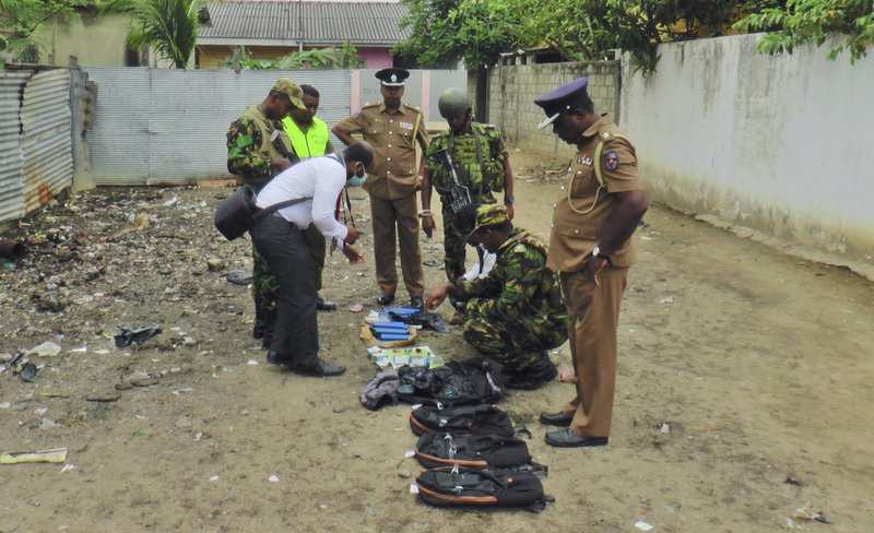 Sri Lankan police and army officers display gelatin sticks, detonators, back packs and other bomb making material recovered from the hide out of militants after Friday's gun battle in Kalmunai, in eastern Sri Lanka Sri Lanka, Saturday, April 27, 2019. (AP Photo/Achala Upendra)