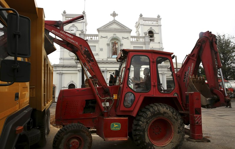 An earth-mover removes the debris from the outside of the damaged St. Anthony's Church after it was targeted in a series of Islamic State-claimed suicide bombings that killed hundreds of people during Easter Sunday, in Colombo, Saturday, April 27, 2019. (AP Photo/Manish Swarup)