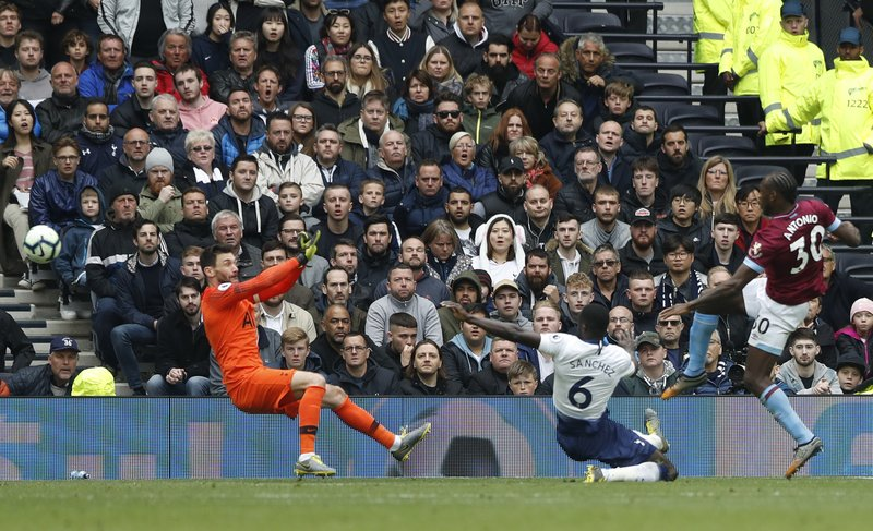 West Ham's Michail Antonio, right, scores the opening goal during the English Premier League soccer match between Tottenham Hotspur and West Ham United at White Hart Lane in London, Saturday, April, 27, 2019. (AP Photo/Alastair Grant)