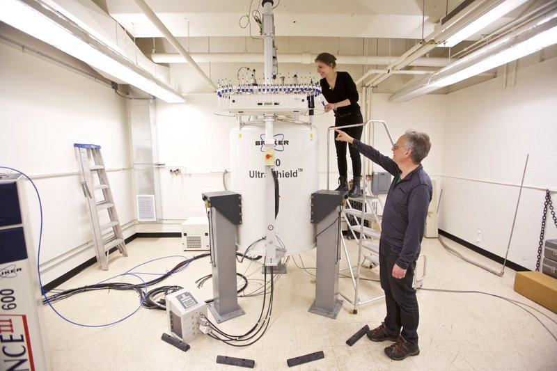 Graduate student Anna Duell, top, and Dr. David Peyton collect samples from a nuclear magnetic resonance spectrometer in a lab at Portland State University in Portland, Ore. (AP Photo/Craig Mitchelldyer)