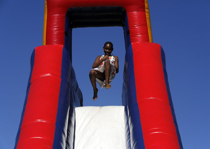 A child plays on an inflatable slide at Freedom Day celebrations in Kwa-Thema Township, near Johannesburg, Saturday April 27, 2019. (AP Photo/Denis Farrell)