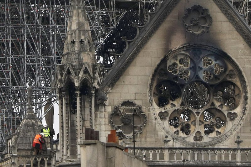 Experts inspect the damaged Notre Dame cathedral after the fire in Paris, Tuesday, April 16, 2019. Experts are assessing the blackened shell of Paris' iconic Notre Dame cathedral to establish next steps to save what remains after a devastating fire destroyed much of the almost 900-year-old building. (AP Photo/Kamil Zihnioglu)