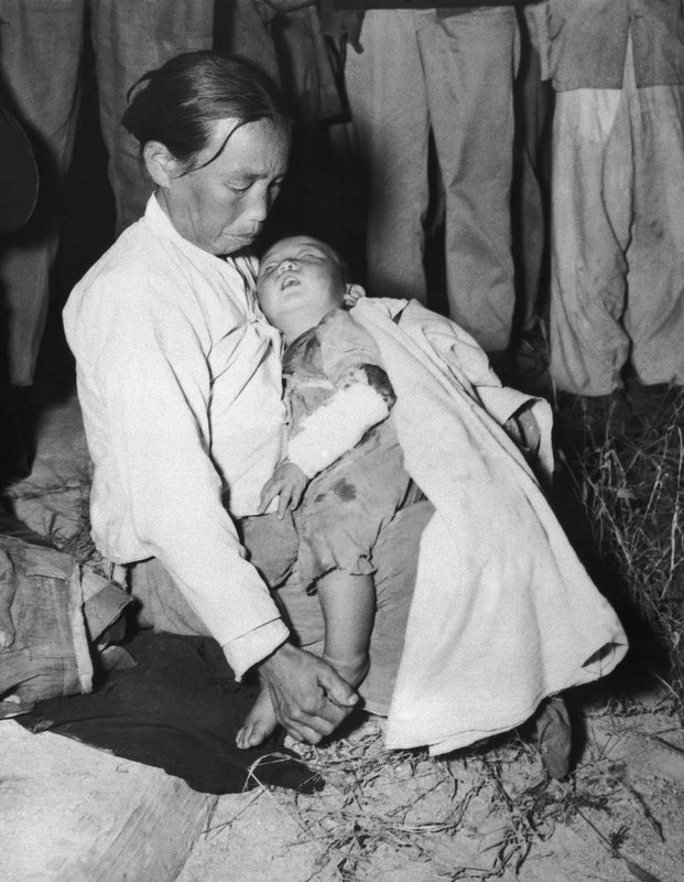 FILE - In this Oct. 17, 1951 file photo, a mother cradles her injured son in her arms as she sits on the ground at Panmunjom, Korea. (AP Photo,File)