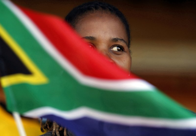 A woman waves a South African flag as she attends Freedom Day celebrations in Kwa-Thema Township, near Johannesburg, Saturday April 27, 2019. (AP Photo/Denis Farrell)