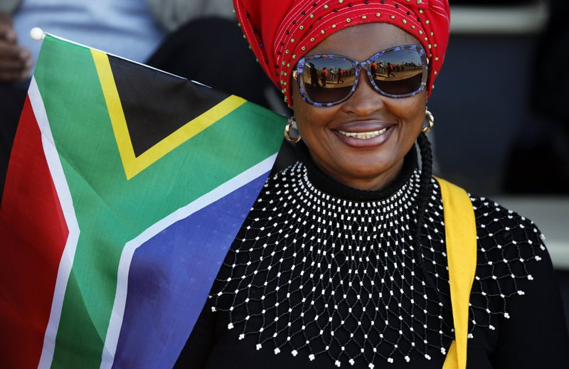 A woman with the South African flag attends Freedom Day celebrations in Kwa-Thema Township, near Johannesburg, Saturday April 27, 2019. (AP Photo/Denis Farrell)