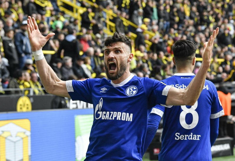 Schalke's Daniel Caligiuri celebrates after he scored his side's third goal during the German Bundesliga soccer match between Borussia Dortmund and FC Schalke 04 in Dortmund, Germany, Saturday, April 27, 2019. (AP Photo/Martin Meissner)