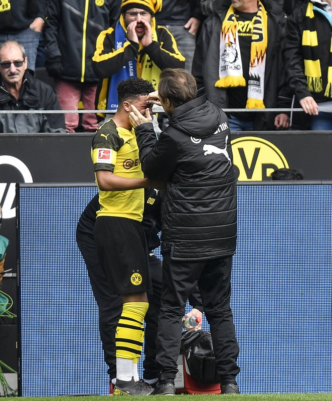 Dortmund's Jadon Sancho gets treatment after he was hit by a pocket lighter during the German Bundesliga soccer match between Borussia Dortmund and FC Schalke 04 in Dortmund, Germany, Saturday, April 27, 2019. (AP Photo/Martin Meissner)